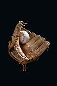 Baseball mitt and ball against black background