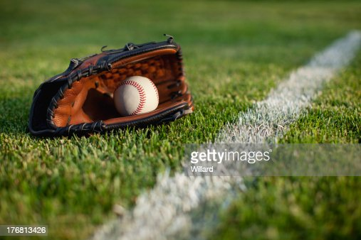 Baseball mitt and ball in grass with selective focus : Stock Photo