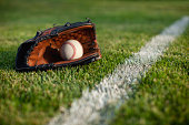 Baseball mitt with ball in grass with white stripe on defocused foreground and backgroundOther baseball images