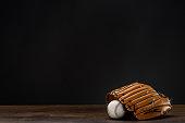 Closeup shot of baseball mitt and ball placed on wooden surface