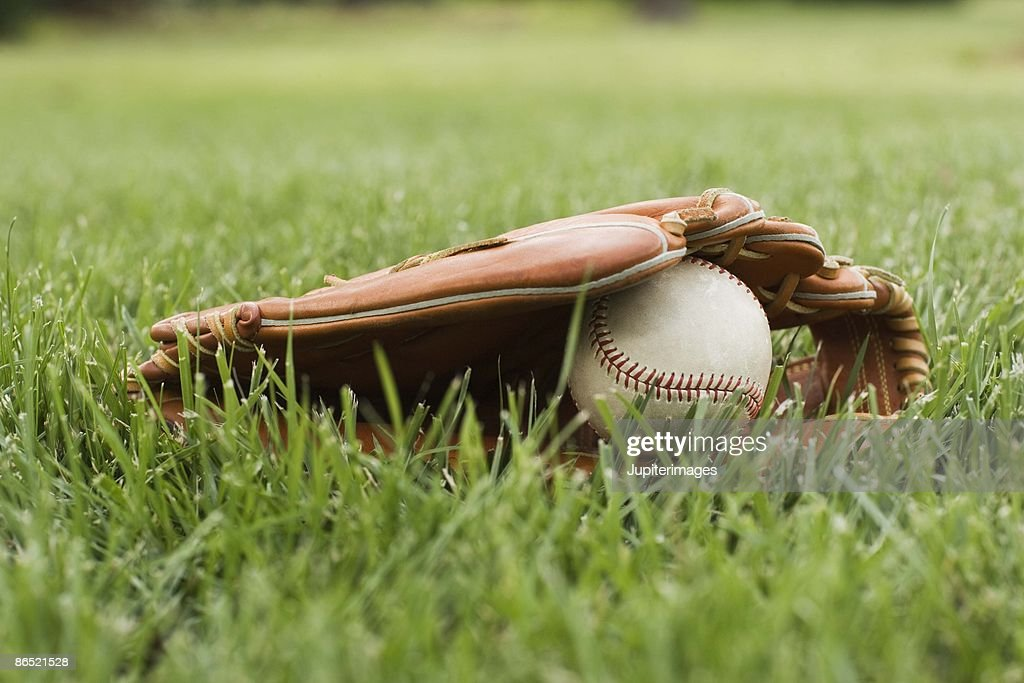 Baseball mitt with ball in grass
