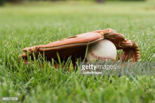 Baseball mitt with ball in grass