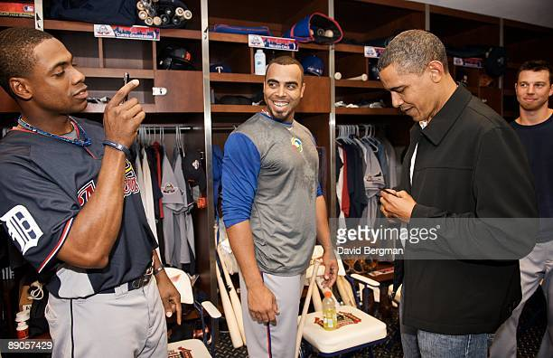 MLB All Star Game United States President Barack Obama autographs a ball for Texas Rangers Nelson Cruz while Detroit Tigers Curtis Granderson takes a...
