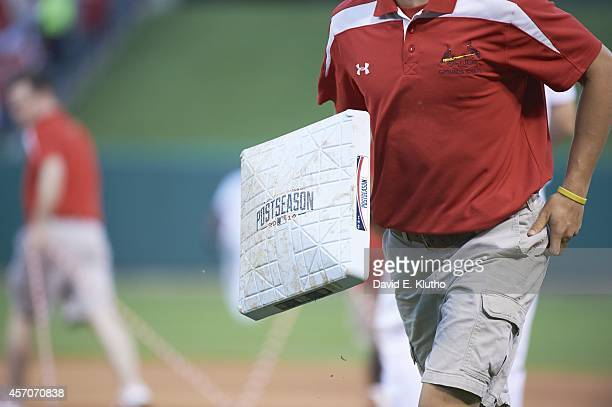 NLDS Playoffs Closeup view of Busch Stadium groudskeeper holding base with POSTSEASON 2014 logo duirng St Louis Cardinals vs Los Angeles Dodgers game...
