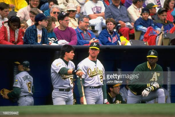 Oakland Athletics Mark McGwire with Jose Canseco in dugout during game vs Texas Rangers Arlington TX 4/18/1992 CREDIT John Biever
