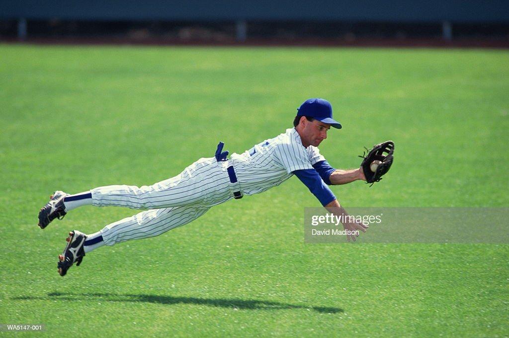Baseball outfielder diving to catch ball