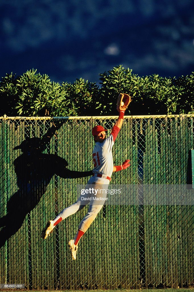 Baseball, outfielder making a leaping catch by fence