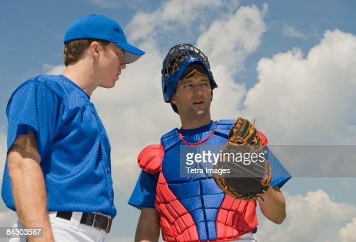 Baseball pitcher and catcher conferring about pitch