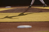 Baseball pitcher and shadow on mound, low section