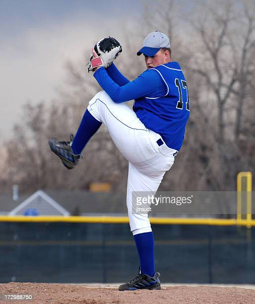 A baseball pitcher in blue getting ready to throw