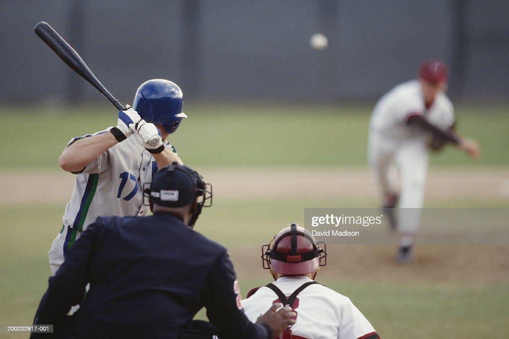 Baseball pitcher pitching ball toward batter, catcher and umpire