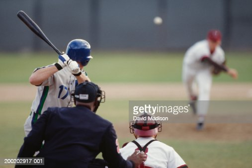 Baseball pitcher pitching ball toward batter, catcher and umpire