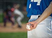 Baseball pitcher preparing to pitch ball
