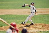 Baseball pitcher preparing to pitch ball to batter