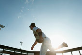 Baseball pitcher throwing pitch, backlit