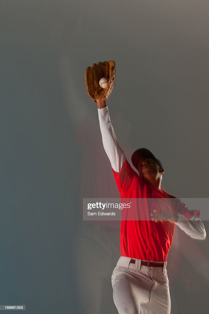 Baseball player catching ball in glove