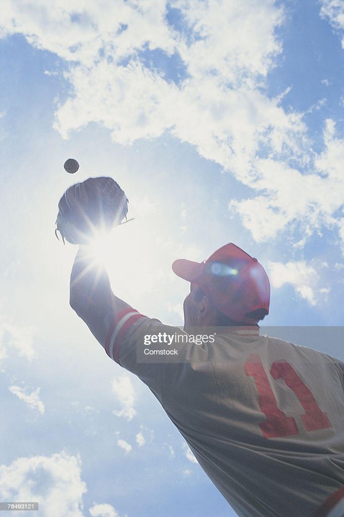 Baseball player catching ball with sun in his eyes