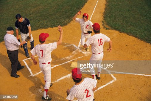 Baseball player crossing home plate greeted by teammates
