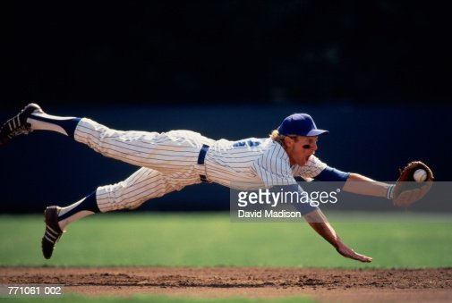 Baseball player diving to catch ball : Stock Photo