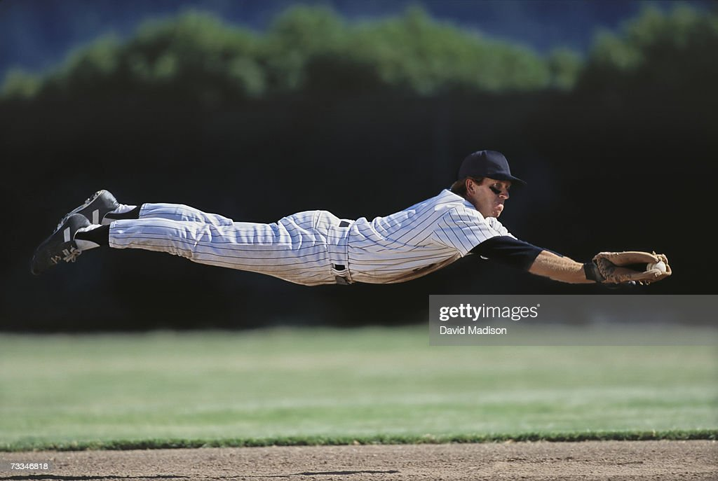 Baseball player diving to catch ball, side view
