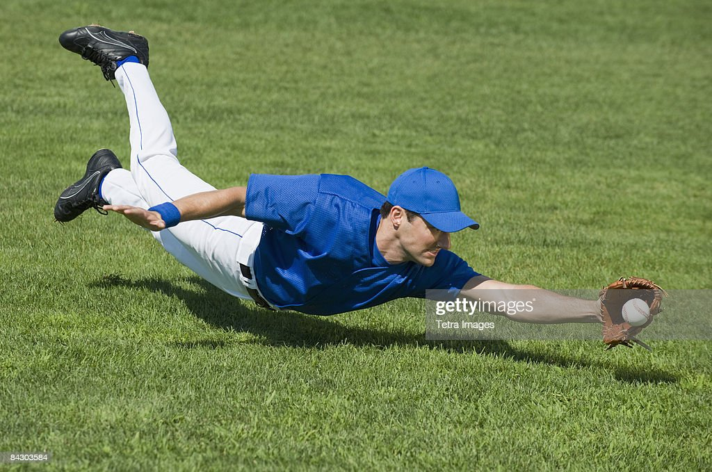 Baseball player diving to catch baseball