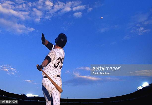 Baseball player hitting ball out of stadium, rear view (Composite)