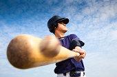 young baseball player hitting the ball