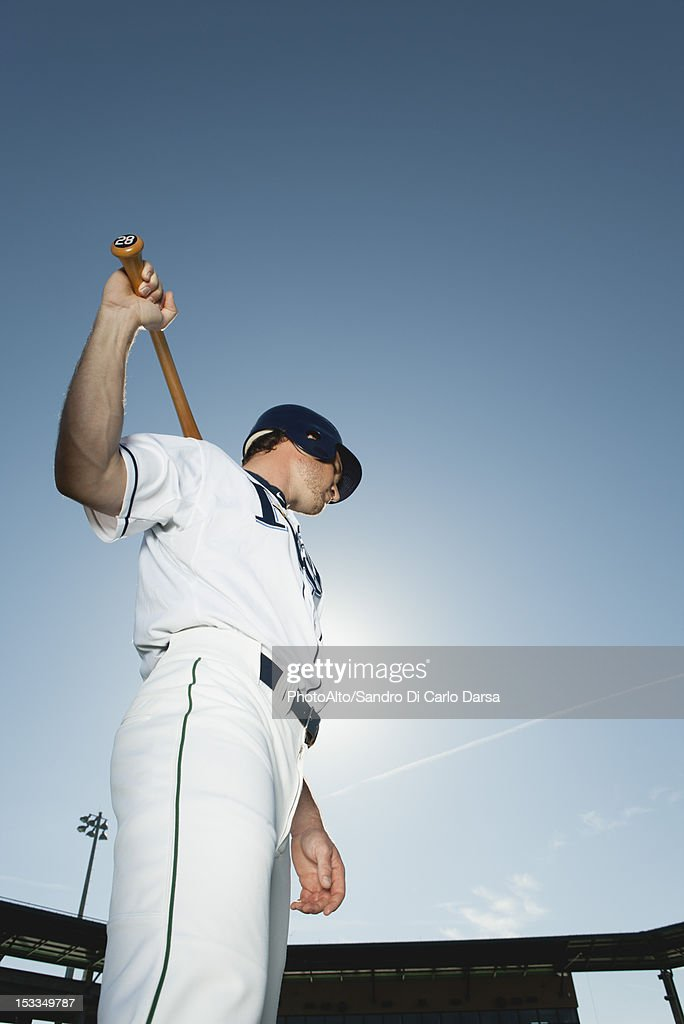 Baseball player holding baseball bat across shoulders : Stock Photo