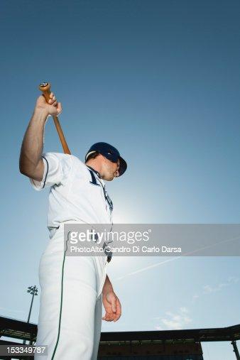 Baseball player holding baseball bat across shoulders : Stock Photo