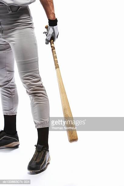 Baseball player holding baseball bat, low section