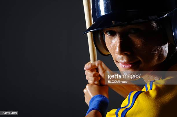 Baseball player holding bat, portrait, close-up, studio shot