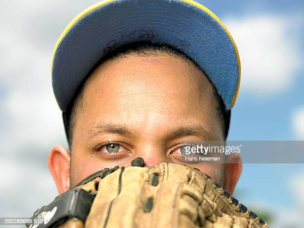 Baseball player holding glove to face, portrait, close-up