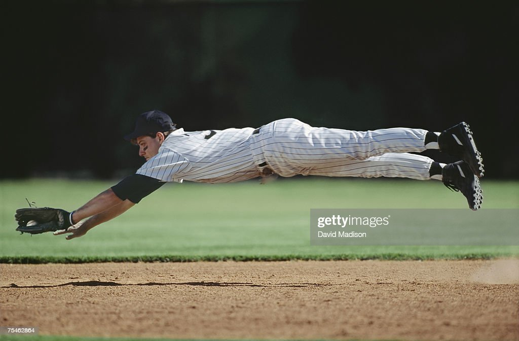 Baseball player in mid-air catching ball. California, USA.