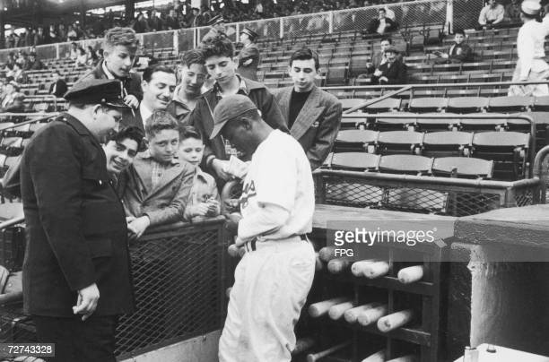 Baseball player Jackie Robinson signs autographs for Brooklyn Dodger's fans late 1940s