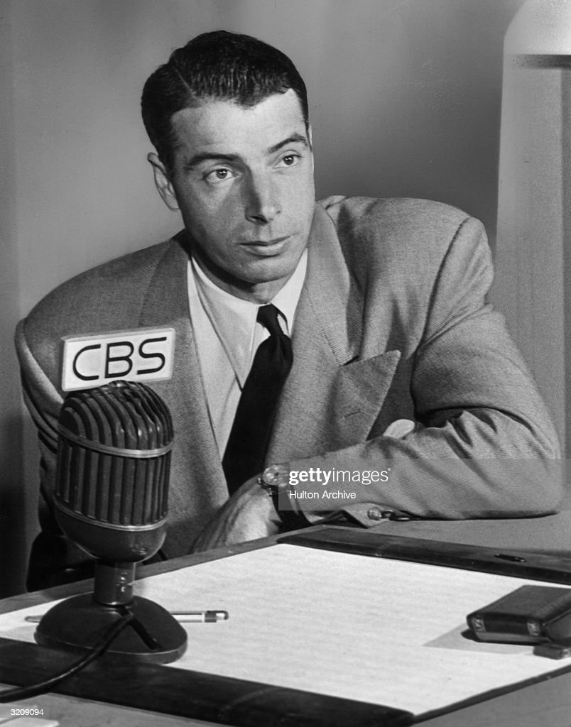 Baseball player Joe DiMaggio sits behind a CBS microphone as the star of the radio series 'The Joe DiMaggio Show'