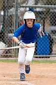 Youth baseball player in blue uniform and white helmet running up the base line with bat in hand.
