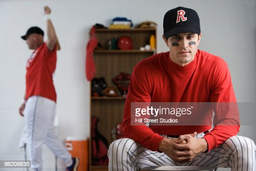 Baseball Player Holding Bat In Locker Room Stock Photo