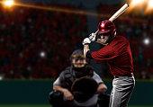 Baseball Player with a red uniform on baseball Stadium.