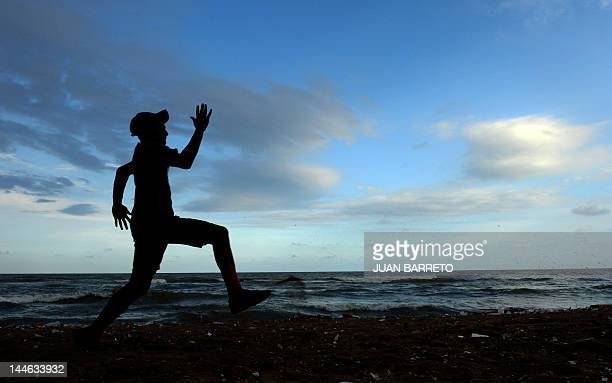 A baseball player practices in the beach of Santo Domingo on May 16 2012 Dominican Republic will hold presidential elections on May 20 AFP PHOTO/JUAN...