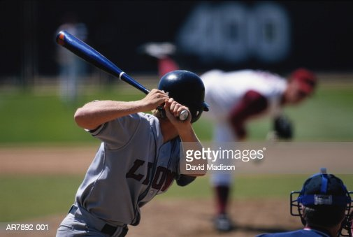 Baseball player preparing to strike ball, pitcher in background : Stock Photo