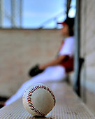A baseball player sits on dugout bench