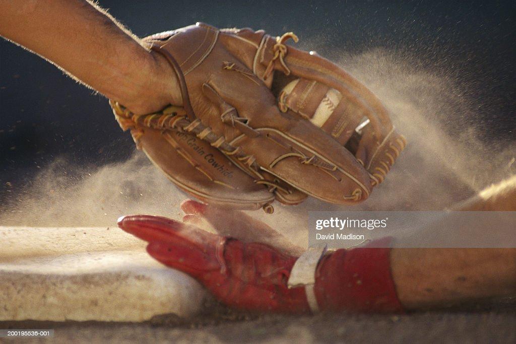 Baseball player sliding into base, baseman tagging player, close-up