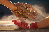 Baseball player sliding into base, baseman tagging player, close-up