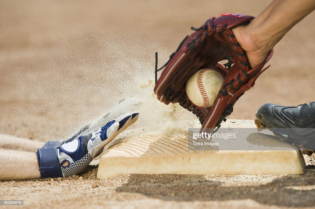 Baseball player sliding into home base