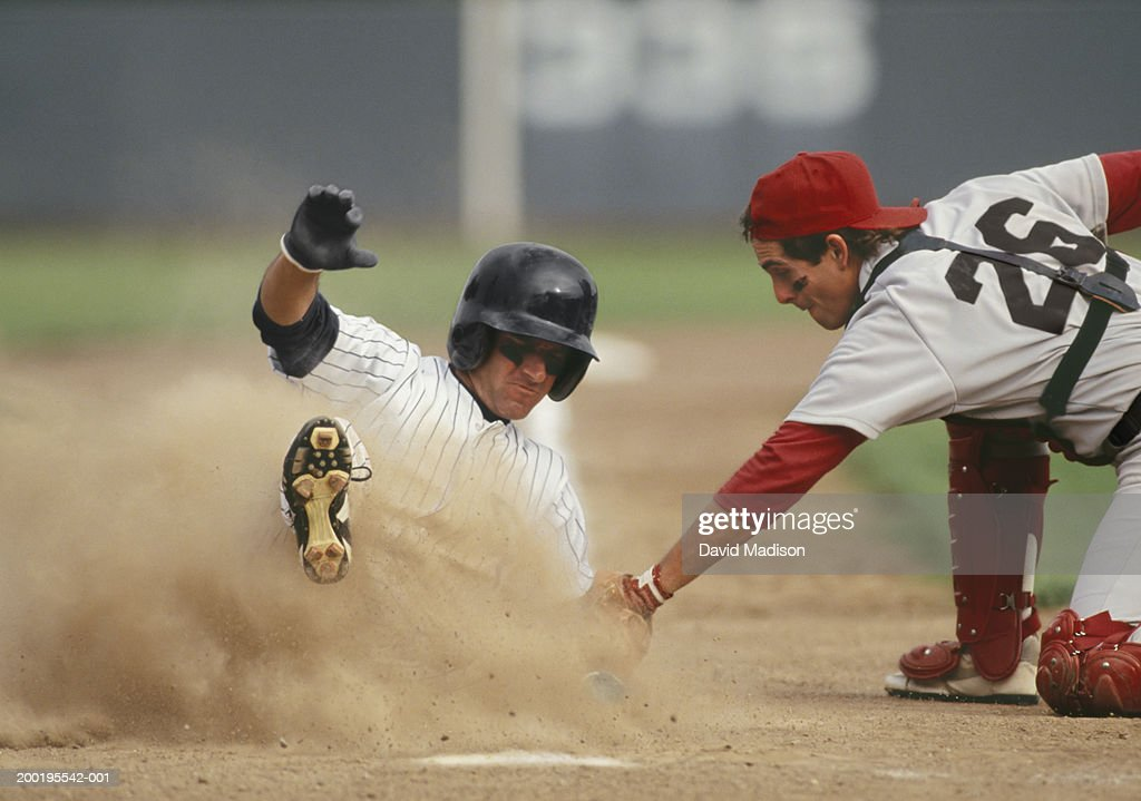 Baseball player sliding into home plate, being tagged by catcher