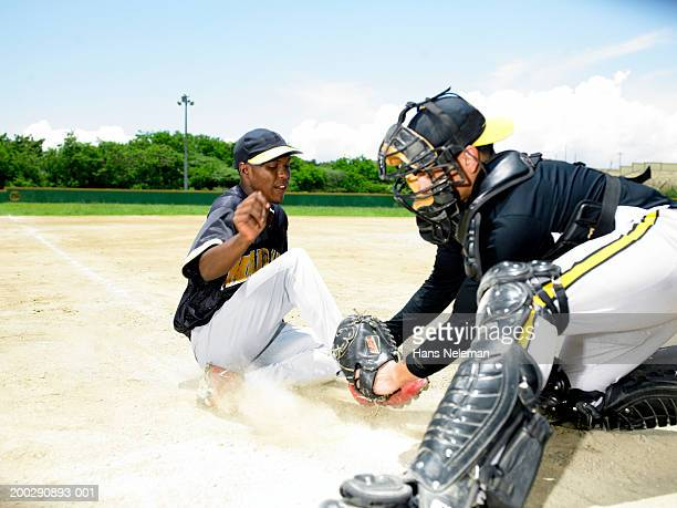 Baseball player sliding into home plate, side view