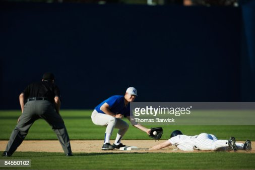Baseball player sliding into second base
