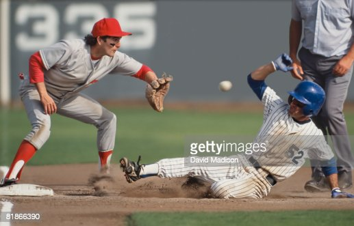 Baseball player sliding into third base with umpire behind him and fielder in process of catching ball.