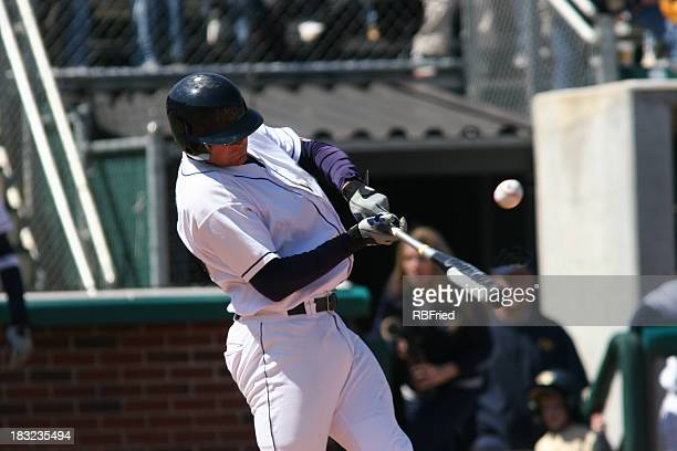 A baseball player up at bat, about to hit the ball