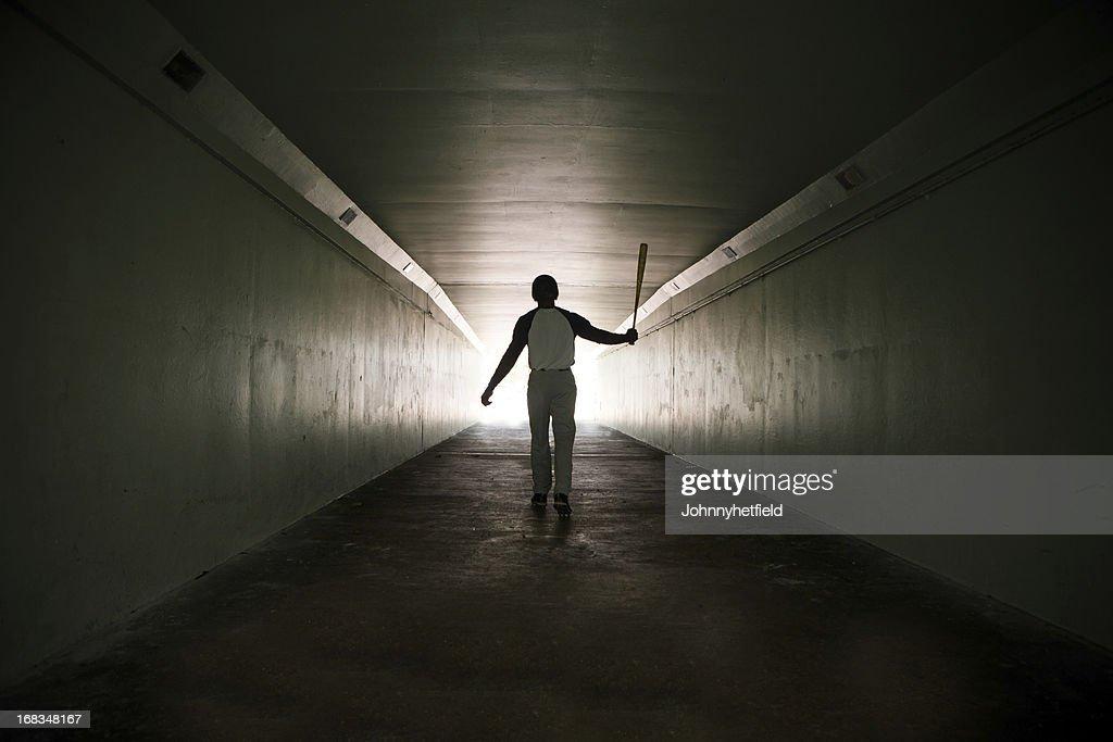 Baseball player walking out of stadium tunnel swinging bat